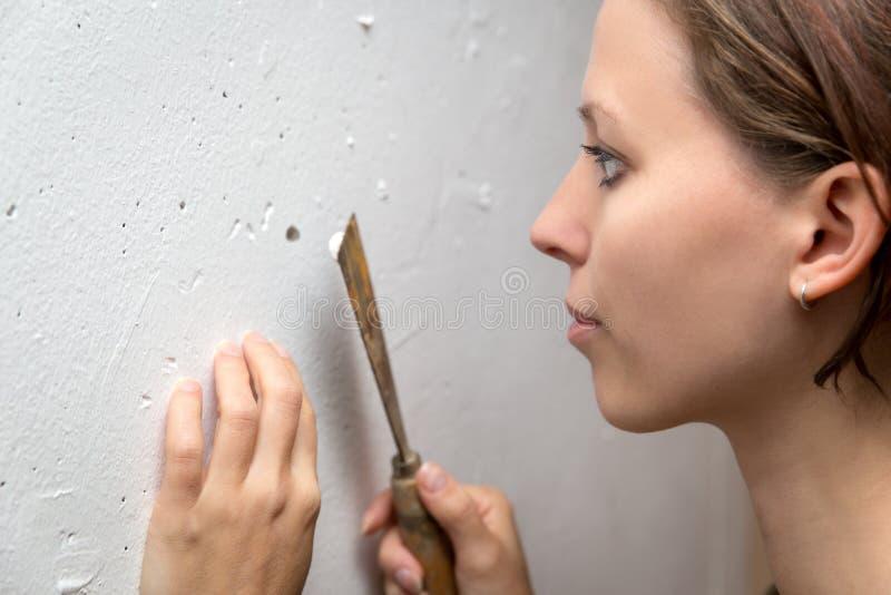 Jovem mulher com uma faca de massa de vidraceiro que repara uma parede, renovação em casa fotos de stock