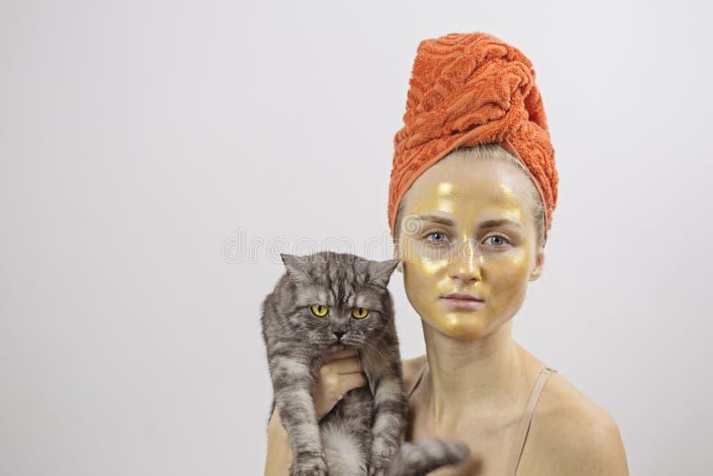 Jovem mulher com uma máscara cosmética dourada em sua cara foto de stock royalty free