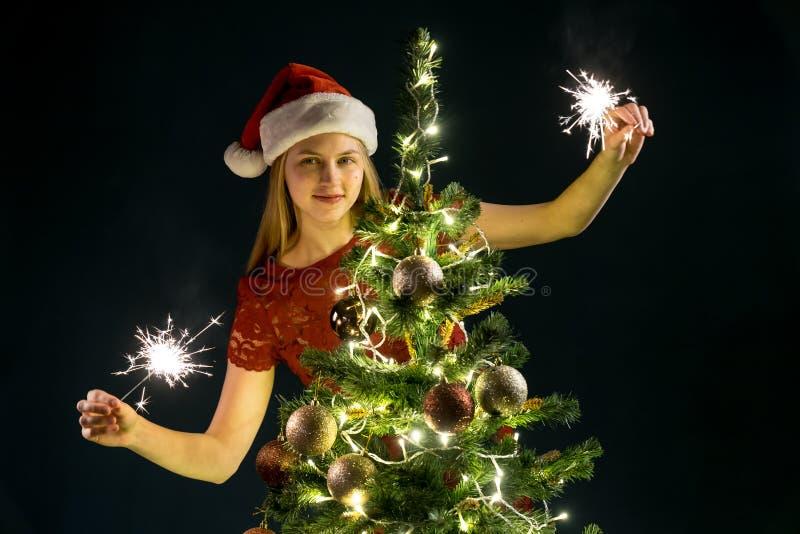 Jovem mulher com velas efervescentes, árvore de Natal e fundo decorativo do bokeh da iluminação Duende e abeto vermelho com decor imagens de stock royalty free