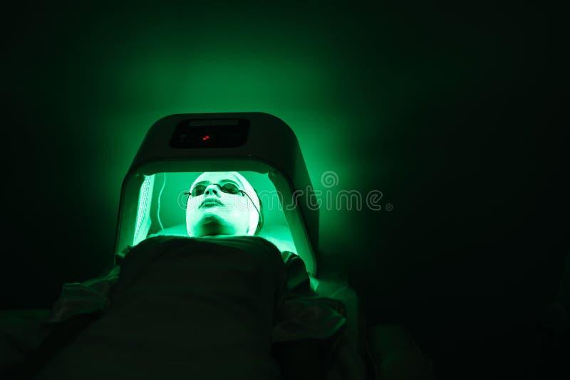 A jovem mulher com vidros da máscara e do solário está relaxando no solário com luz verde no salão de beleza Cuidado de pele foto de stock royalty free