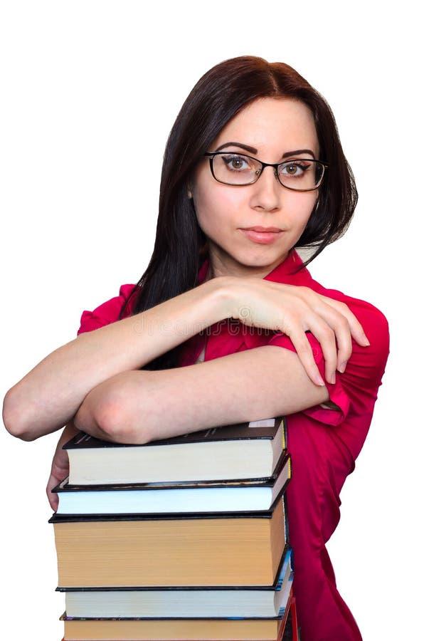 Jovem mulher com vidros e pilha de livros isolados no fundo branco imagens de stock