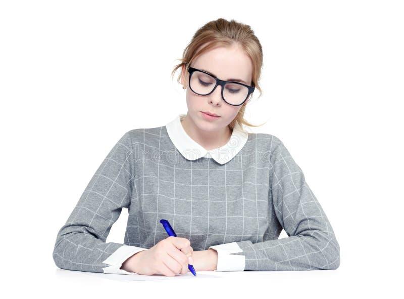 A jovem mulher com vidros escreve a pena no papel, no fundo branco foto de stock royalty free