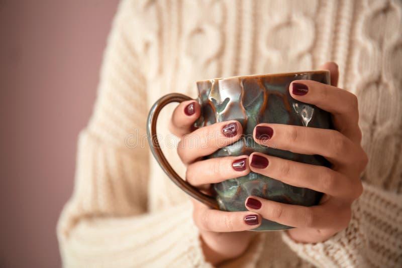 Jovem mulher com a xícara de café bonita da terra arrendada do tratamento de mãos, close up imagem de stock
