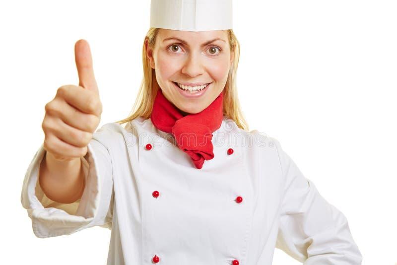Jovem mulher como o cozinheiro do cozinheiro chefe que mantém o polegar imagens de stock royalty free