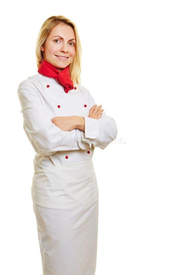 Jovem mulher como o cozinheiro no workwear foto de stock