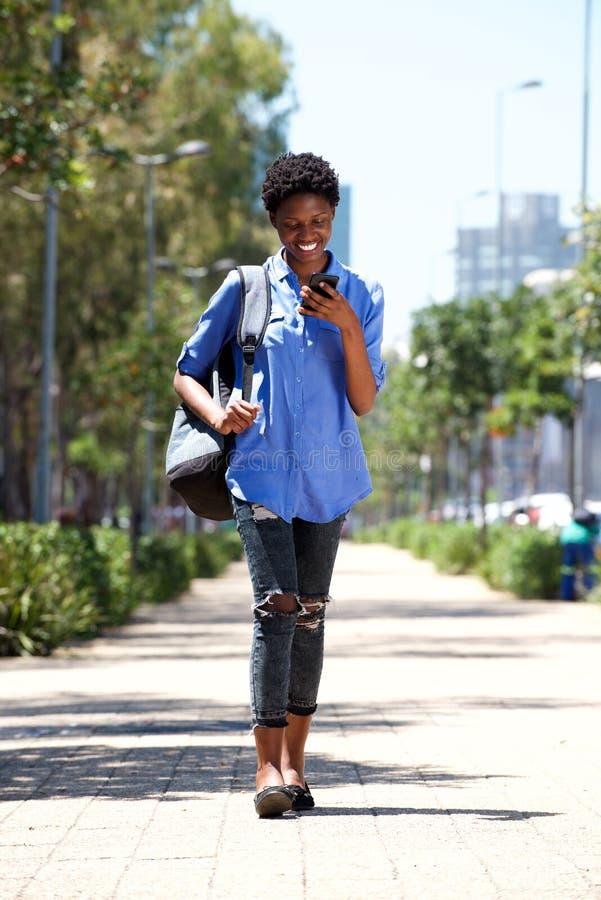 Jovem mulher completa do comprimento que anda abaixo da rua com telefone celular imagem de stock royalty free