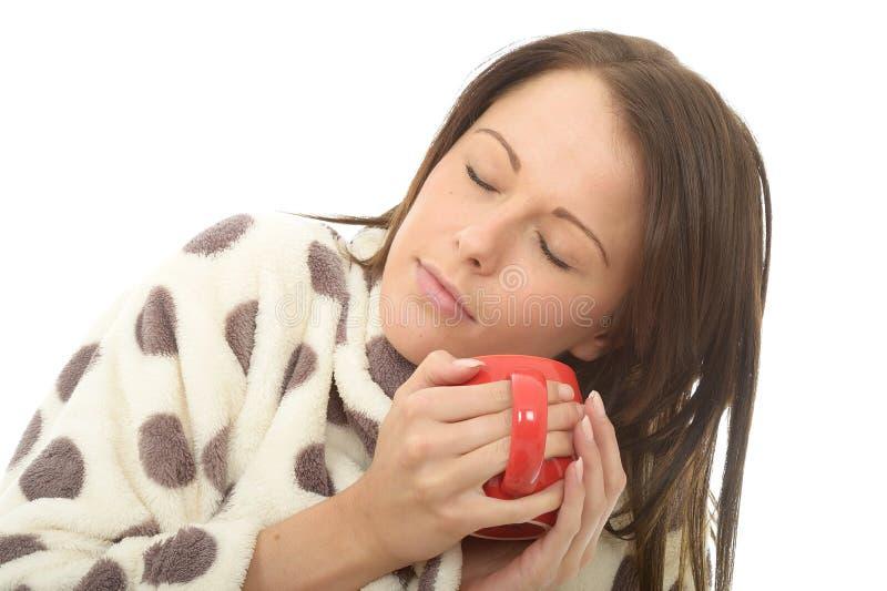 Jovem mulher confortável cansado relaxado atrativa que guarda um copo do chá imagens de stock royalty free