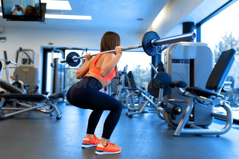 Jovem mulher consider?vel magro em ocupas do sportswear com um barbell no ombro no gym imagem de stock royalty free