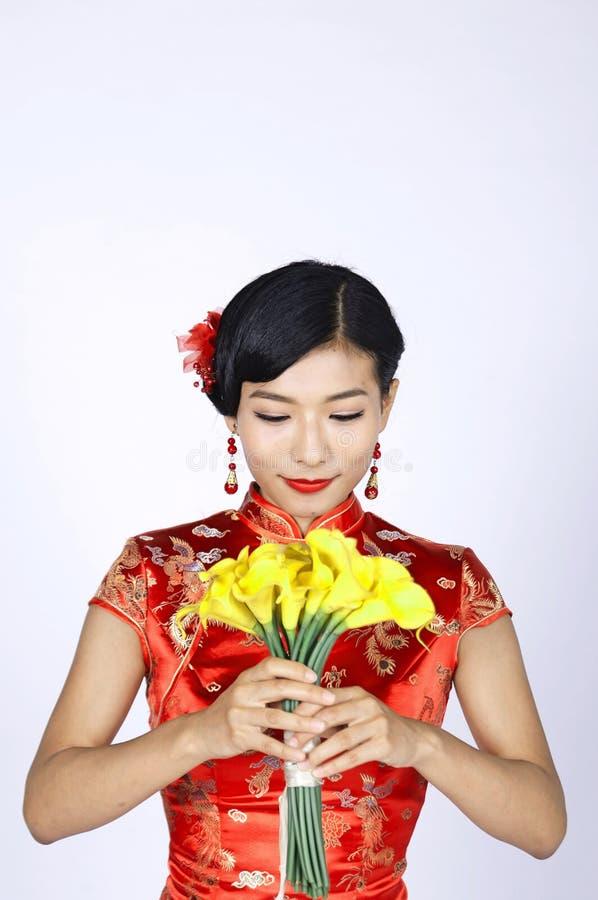 Jovem mulher consideravelmente chinesa que guarda um grupo de narcisos amarelos amarelos imagens de stock