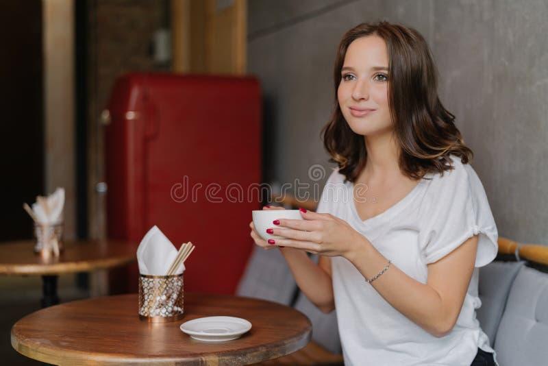 A jovem mulher consideravelmente despreocupada na camisa ocasional do branco t, tem a cara feliz, bebe o café aromático, passa o  imagem de stock