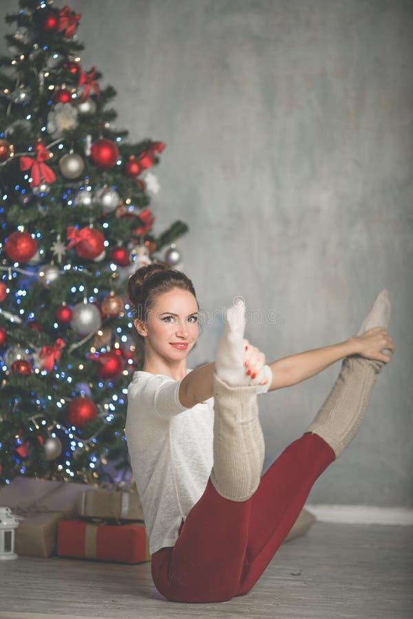 A jovem mulher consideravelmente flexível está fazendo esportes perto da árvore de Natal, esportes e conceito do feriado fotografia de stock royalty free