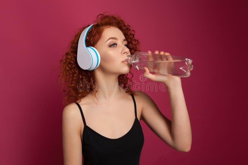 A jovem mulher consideravelmente saudável que bebe o mineral puro engarrafou a água em um fundo cor-de-rosa foto de stock royalty free