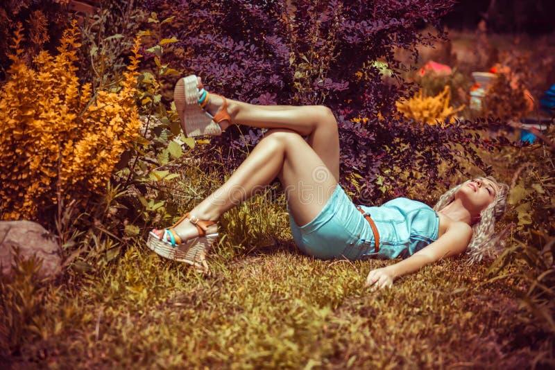 Jovem mulher consideravelmente 'sexy' que encontra-se na grama fotografia de stock