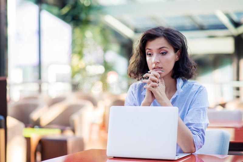 Jovem mulher contemplada no caf? com port?til fotografia de stock royalty free