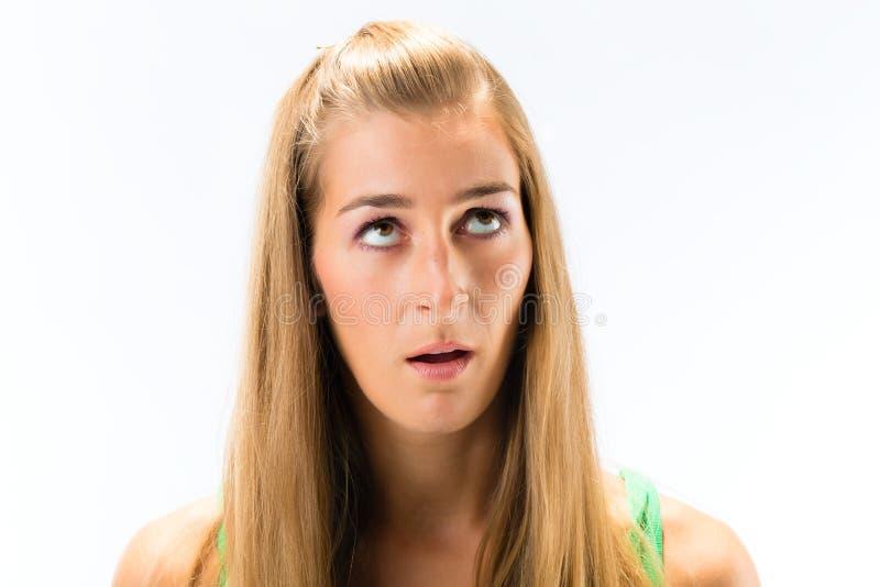 Jovem mulher contemplada que olha acima imagens de stock