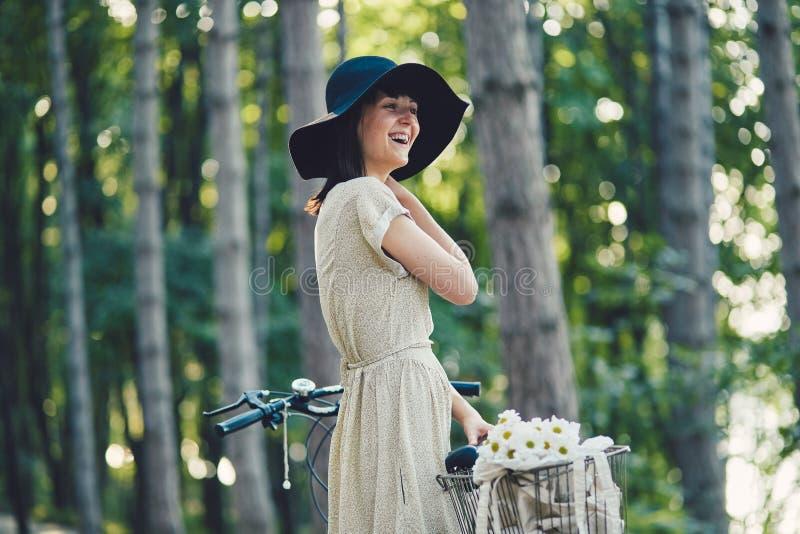 Jovem mulher contra o fundo da natureza com bicicleta fotos de stock royalty free