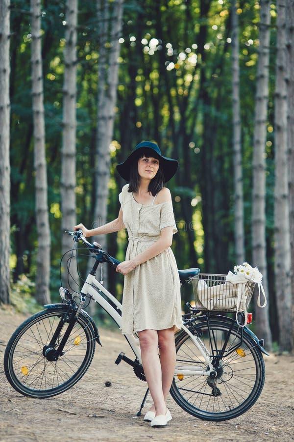 Jovem mulher contra o fundo da natureza com bicicleta imagem de stock royalty free