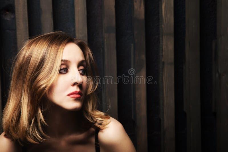 Jovem mulher contra uma parede de madeira foto de stock royalty free