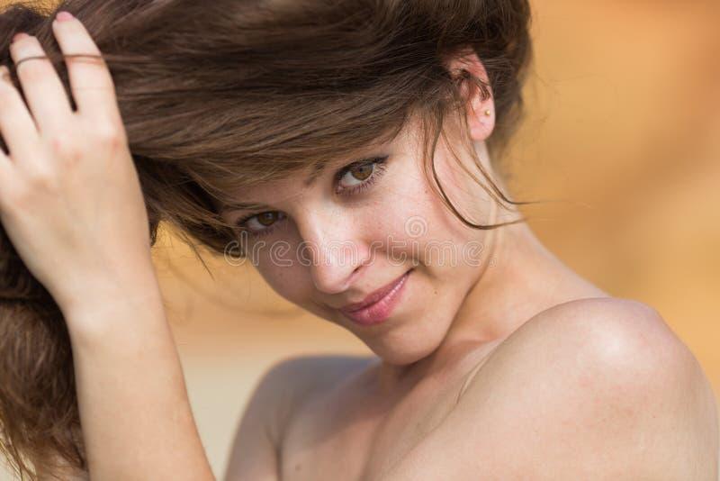 A jovem mulher corrige-a hairstile imagens de stock