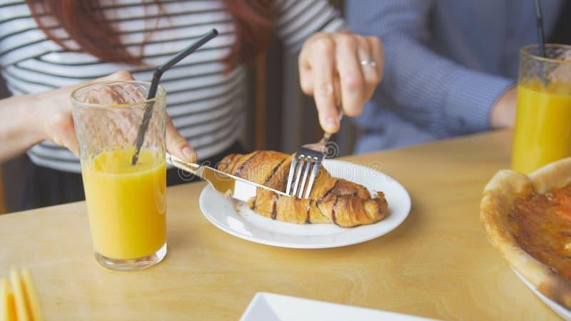 A jovem mulher corta um croissant saboroso com uma faca e uma forquilha que come no restaurante foto de stock