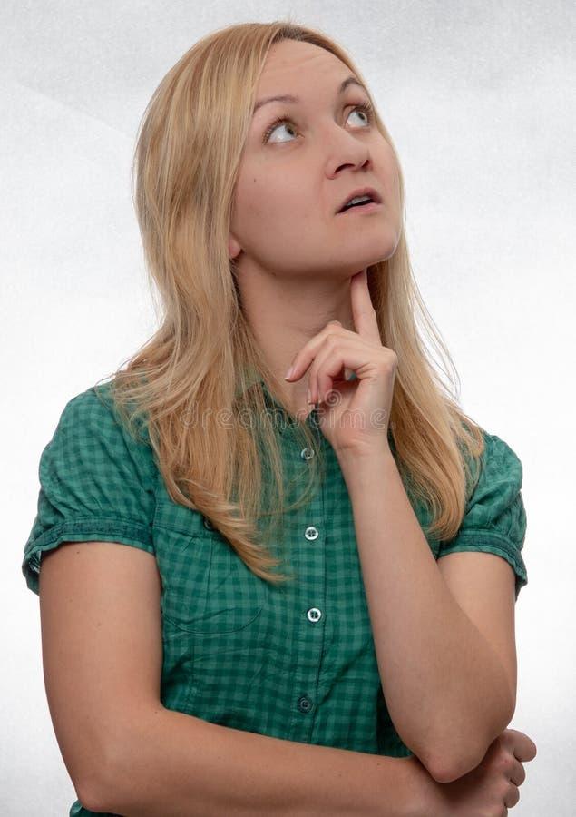 Jovem mulher curiosa na camisa verde ocasional que olha acima e certo imagens de stock royalty free