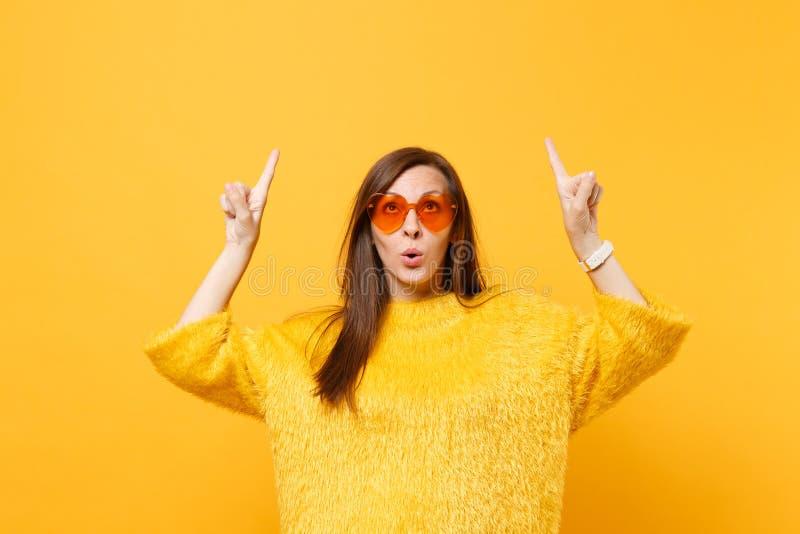 Jovem mulher curiosa na camiseta da pele e em vidros alaranjados do coração que aponta os indicadores acima no espaço da cópia is fotografia de stock