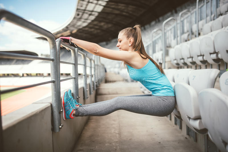 Jovem mulher da aptidão que estica outddors, fazendo excercises da ginástica e aquecer-se fotografia de stock royalty free