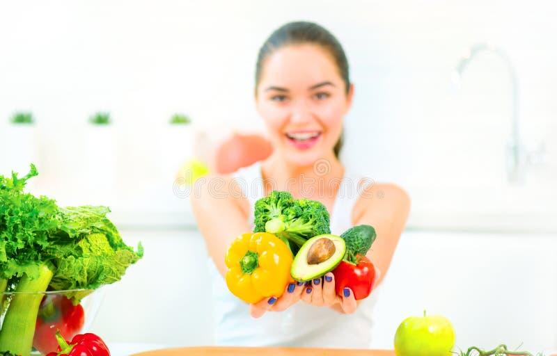 Jovem mulher da beleza que guarda legumes frescos e frutos em sua cozinha em casa foto de stock