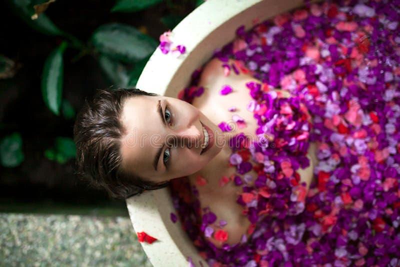 Jovem mulher da beleza que relaxa no banho exterior com flor tropical fotografia de stock royalty free