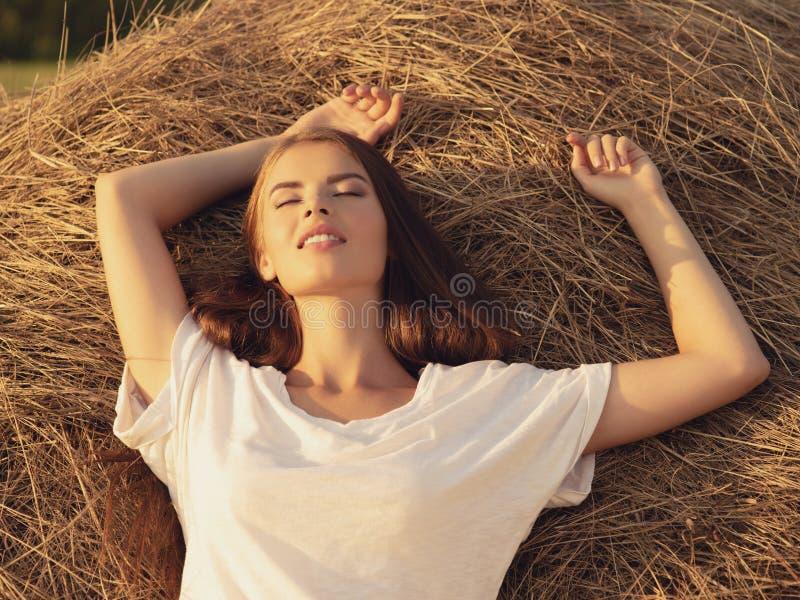 A jovem mulher da calma est? relaxando no monte de feno imagens de stock