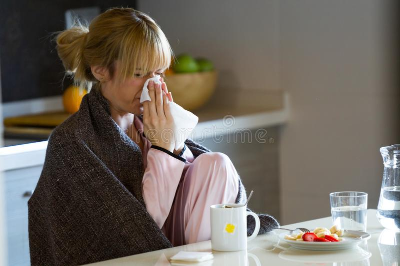 Jovem mulher da doença que espirra em um tecido em casa fotos de stock royalty free