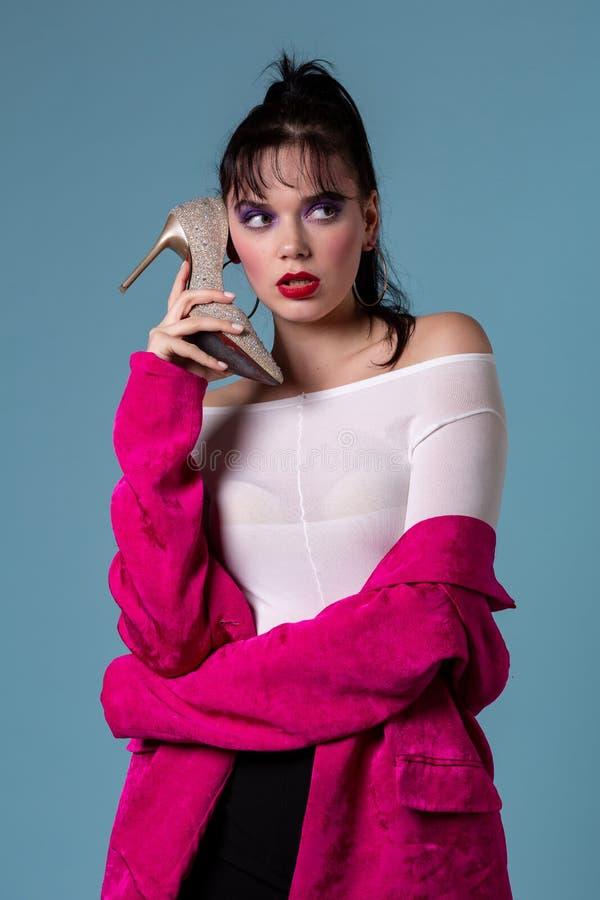 Jovem mulher da forma com composição colorida usando uma sapata do salto alto como um telefone fotos de stock royalty free