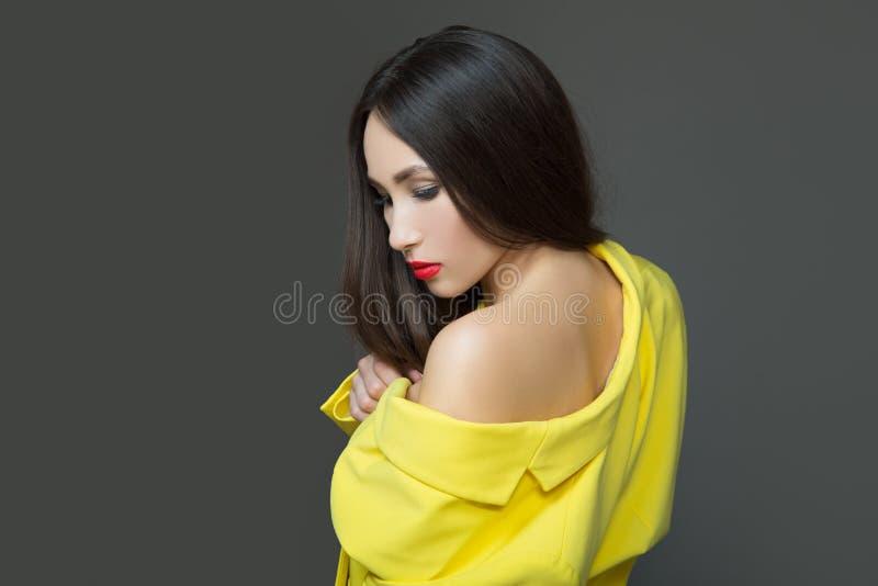 Jovem mulher da forma na roupa amarela Cabelo luxuoso longo e batom vermelho Fundo escuro fotografia de stock