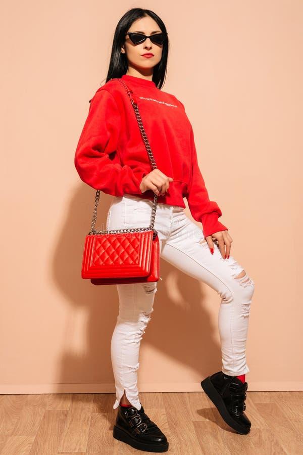 Jovem mulher da forma nas calças de brim e na camiseta brancas com a embreagem vermelha do saco nas mãos imagens de stock
