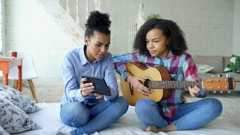 Jovem mulher da raça misturada com o tablet pc que senta-se na cama que ensina sua irmã adolescente jogar em casa a guitarra acús fotos de stock royalty free