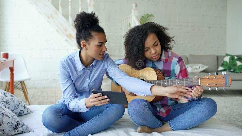 Jovem mulher da raça misturada com o tablet pc que senta-se na cama que ensina sua irmã adolescente jogar em casa a guitarra acús foto de stock royalty free