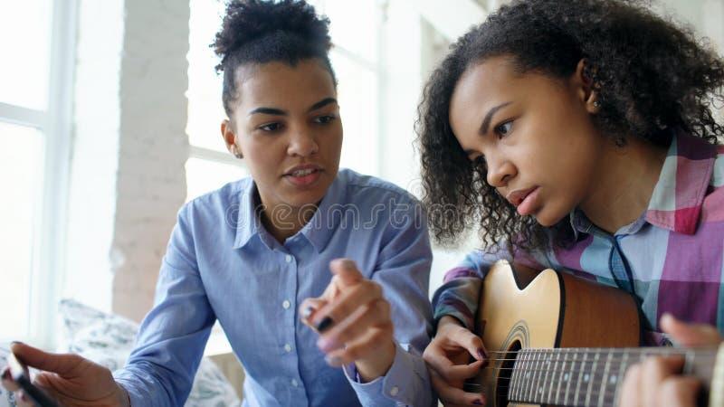 Jovem mulher da raça misturada com o tablet pc que senta-se na cama que ensina sua irmã adolescente jogar em casa a guitarra acús foto de stock