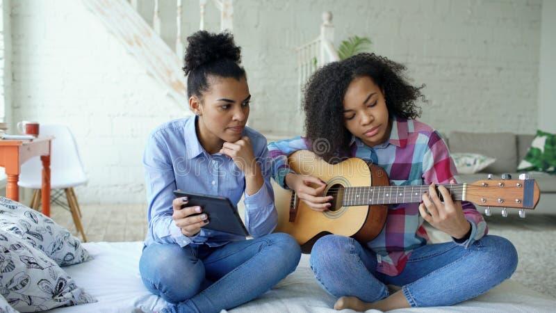 Jovem mulher da raça misturada com o tablet pc que senta-se na cama que ensina sua irmã adolescente jogar em casa a guitarra acús fotografia de stock
