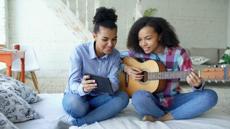 Jovem mulher da raça misturada com o tablet pc que senta-se na cama que ensina sua irmã adolescente jogar em casa a guitarra acús fotos de stock