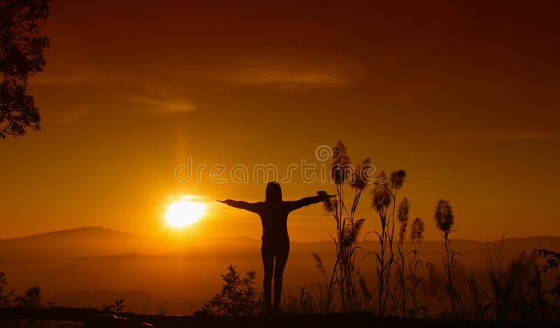A jovem mulher da silhueta do por do sol que sente à liberdade e relaxa imagem de stock
