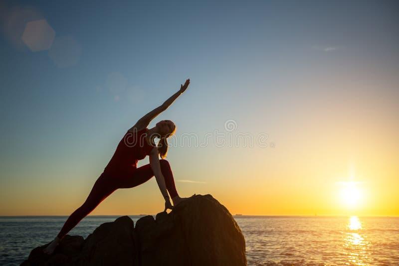 Jovem mulher da silhueta da ioga que faz exercícios da aptidão imagens de stock royalty free