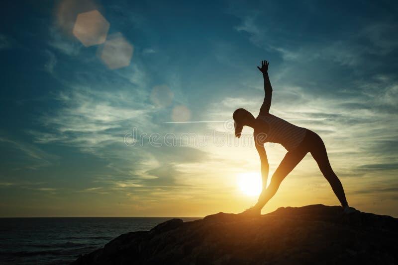 Jovem mulher da silhueta da ioga que faz exerc?cios da aptid?o na praia foto de stock royalty free