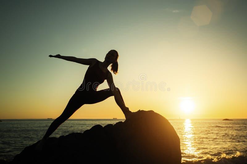 Jovem mulher da silhueta da ioga que faz exerc?cios da aptid?o na praia fotografia de stock