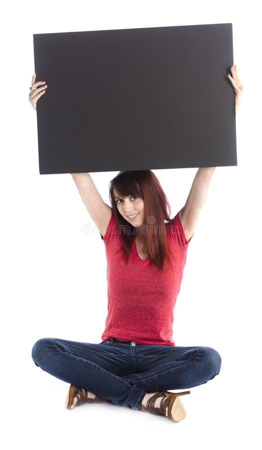 Jovem mulher de assento que aumenta o cartão preto vazio imagem de stock