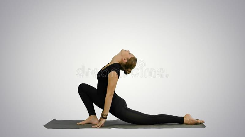 A jovem mulher de Bbeautiful que vestem o sportswear preto que dá certo, fazendo a ioga ou os pilates exercitam no fundo branco imagens de stock