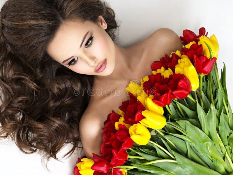 Jovem mulher de Beauitful com o ramalhete das flores fotos de stock royalty free