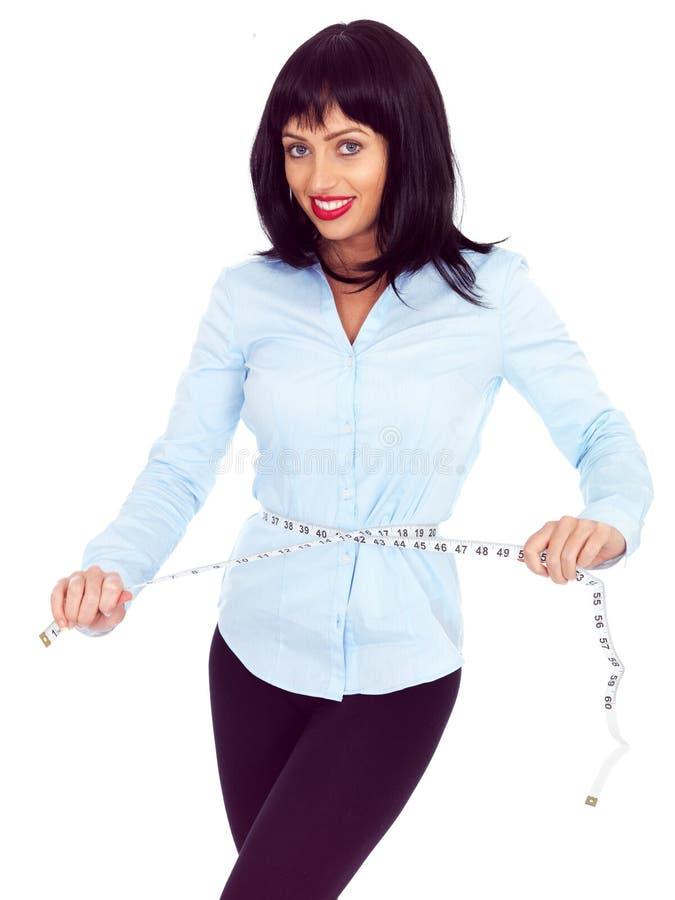 Jovem mulher de cabelo escura atrativa que verifica sua medida de cintura com uma fita métrica fotos de stock royalty free