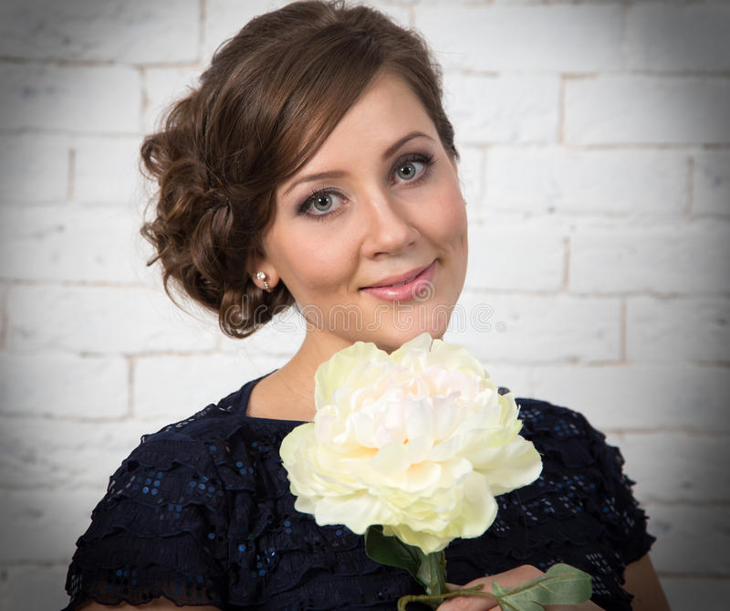 Jovem mulher de cabelo escura muito bonita com flor branca fotos de stock