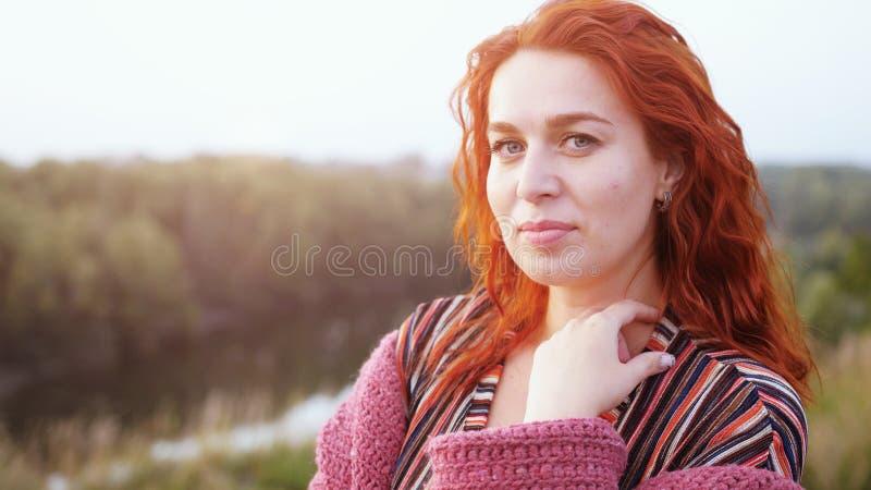 Jovem mulher de cabelo vermelha bonita que levanta no campo no por do sol imagens de stock