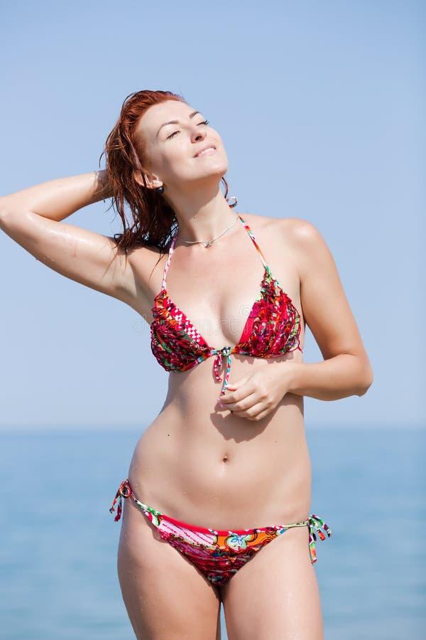 Jovem mulher de cabelo vermelha no biquini que seca seu cabelo na praia imagens de stock